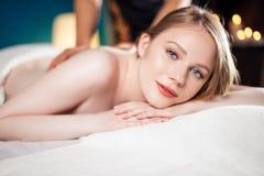 Красивая, молодая и здоровая женщина имеет горячий каменный массаж спа 7 стоковые фотографии rf