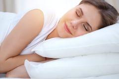 Красивая молодая и счастливая женщина спать пока лежащ в кровати удобно и блаженно усмехающся стоковые фотографии rf