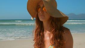 Красивая молодая кавказская женщина в бикини с солнечными очками и положение шляпы на пляже сток-видео
