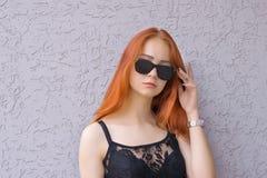 Красивая молодая красная женщина волос в солнечных очках на текстурированной предпосылке Стоковые Изображения RF