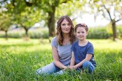 Красивая молодая мать и маленькая дочь сидя на зеленой траве и отдыхать Стоковое Изображение