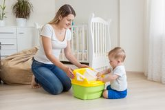 Красивая молодая мать уча ей 10 месяцам старого сына используя бак младенца стоковые фото