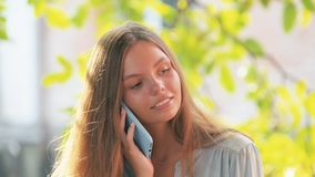 Красивая молодая милая девушка в голубой рубашке с телефоном в outdise голубого случая говоря на съемке конюшни летнего дня сток-видео