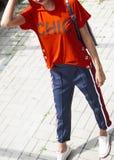 Красивая молодая модельная женщина в красной рубашке с клобуком и голубым trou Стоковое Фото