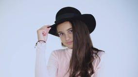 Красивая молодая модель кивает головой в шляпе и смотрит камеру энигматично видеоматериал