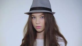 Красивая молодая модель поднимает голову в шляпе и смотрит камеру энигматично видеоматериал