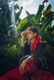 Красивая молодая модная женщина с составляет и стильные аксессуары boho представляя на естественной тропической предпосылке стоковое фото