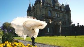 Красивая молодая невеста и красивый groom держа в воздухе outdoors около старого особняка сток-видео