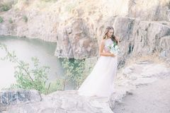 Красивая молодая невеста с длинным белокурым вьющиеся волосы в длинном белом платье в поле лета стоковое фото rf