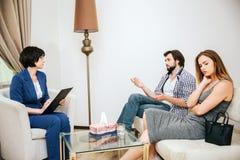 Красивая молодая пара сидит на софе Человек говорит к психологу доктор слушает к нему Девушка расстроена стоковые изображения rf