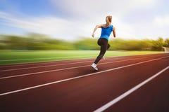Красивая молодая спортсменка бежать на идущем взгляде задней части следа на предпосылке нерезкости Спортсмен бежит вокруг скакать стоковые фото