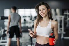 Красивая молодая спортсменка в sportswear и наушниках держит бутылку воды, слушая музыку используя телефон и усмехаться стоковые фото