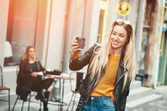 Красивая молодая стильная носка женщины в одеждах моды и оставаться перед кафем и держать черную чашку кофе, Стоковая Фотография RF