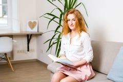 Красивая молодая студентка с длинными красными волосами в розовых юбке и рубашке читая книгу, держа в ее руке усаживание учебника стоковое фото rf