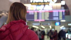 Красивая молодая туристская девушка в международном аэропорте или железнодорожном вокзале, около доски данным по полета акции видеоматериалы
