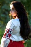 Красивая молодая украинская девушка в национальном костюме Девушка с красивым появлением у древесины на природе Портрет стоковые изображения