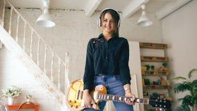 Красивая молодая усмехаясь девушка в наушниках представляя с студией электрической гитары дома внутри помещения Стоковая Фотография RF