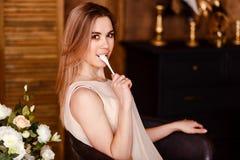 Красивая молодая усмехаясь женщина в бежевом платье держит небольшую ложку в ее рте стоковые изображения rf