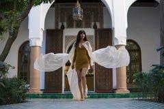 Красивая морокканская девушка идя и развевая ее белая хламида в богатом интерьере живописного Dar Si сказала Riyad внутри стоковая фотография
