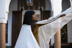 Красивая морокканская девушка развевая ее белая хламида в богатом интерьере живописного Dar Si сказала Riyad в Marrakech стоковые изображения rf