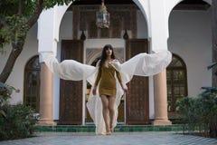 Красивая морокканская девушка развевая ее белая хламида в богатом интерьере живописного Dar Si сказала Riyad в Marrakech стоковые фотографии rf