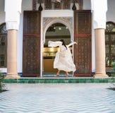 Красивая морокканская девушка развевая ее белая хламида в богатом интерьере живописного Dar Si сказала Riyad в Marrakech стоковое фото