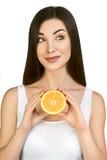 Красивая модельная держа половина сочного апельсина на белой предпосылке Стоковые Изображения