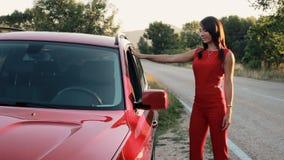 Красивая модель в красном комбинезоне представляя около автомобиля и усмехаться сток-видео