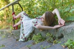 Красивая модель девушки лежит на каменных шагах Стоковые Фотографии RF
