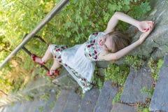 Красивая модель девушки лежит на каменных шагах Стоковые Изображения