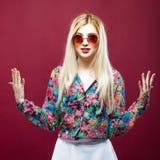 Красивая модель при солнечные очки и длинные волосы нося красочную рубашку на розовой предпосылке Изумительная блондинка представ Стоковая Фотография