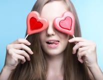 Красивая модель с леденцами на палочке в форме сердца стоковое фото