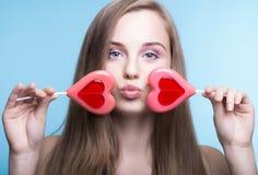 Красивая модель с леденцами на палочке в форме сердца стоковое изображение rf