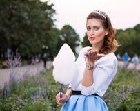 Красивая модная девушка с конфетой хлопка посылает поцелуй в парке в теплом вечере лета Стоковые Фото