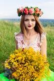 Красивая модная довольно шикарная девушка в платье на поле цветков Славная девушка с венком цветков на ее голове и букете Стоковое Изображение