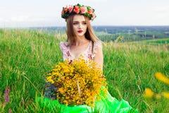 Красивая модная довольно шикарная девушка в платье на поле цветков Славная девушка с венком цветков на ее голове и букете Стоковые Фото