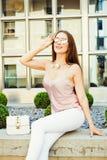 Красивая модно одетая темн-с волосами девушка в солнечных очках представляя на улице на вечере лета на предпосылке  стоковое фото