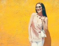Красивая модно одетая темн-с волосами девушка при солнечные очки представляя около фиолетовой стены стоковые изображения