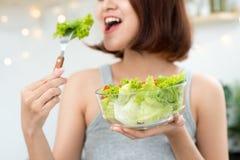 Красивая молодая азиатская девушка есть салат усмехаясь счастливое eati девушки Стоковое Фото