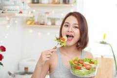 Красивая молодая азиатская девушка есть салат усмехаясь счастливое eati девушки Стоковые Изображения RF