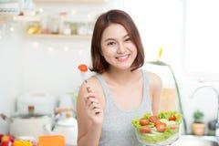 Красивая молодая азиатская девушка есть салат усмехаясь счастливое eati девушки Стоковое Изображение RF