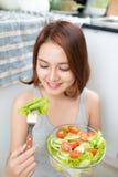 Красивая молодая азиатская девушка есть салат усмехаясь счастливое eati девушки Стоковые Изображения