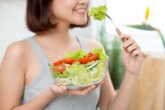 Красивая молодая азиатская девушка есть салат усмехаясь счастливое eati девушки Стоковая Фотография RF