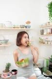 Красивая молодая азиатская девушка есть салат усмехаясь счастливое eati девушки Стоковые Фото