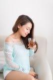 Красивая молодая азиатская женщина выпивая ее чай утра над brea Стоковое Фото