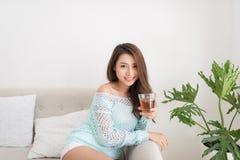 Красивая молодая азиатская женщина выпивая ее чай утра над brea Стоковая Фотография