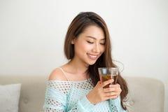 Красивая молодая азиатская женщина выпивая ее чай утра над brea Стоковые Изображения