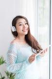 Красивая молодая азиатская женщина выпивая ее чай утра дома Стоковые Изображения RF
