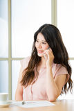 Красивая молодая азиатская женщина используя умный говорить телефона Стоковое фото RF
