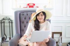 Красивая молодая азиатская женщина дома сидя на роскошном usi софы Стоковые Фотографии RF